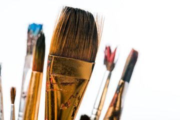 close up of paintbrushes with paint isolated on white
