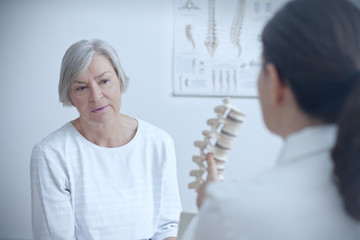 Aging and back pain concept: doctor of orthopedics showing her senior patient a degenerated disk on a backbone model.