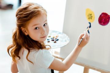 selective focus of cute redhead kid painting in art school