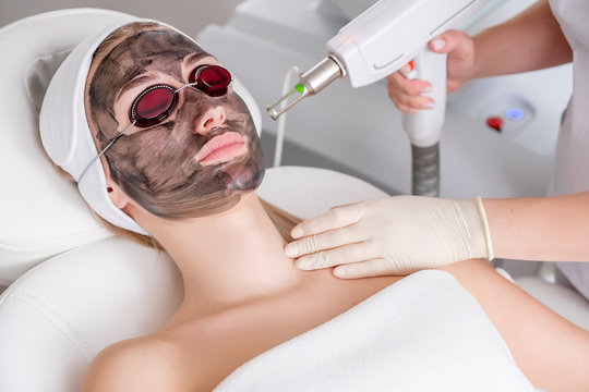 Close-up of a cosmetologist's hand making a hardware carbon peeling by a young pretty customer woman in safety glasses and a headdress lying on a couch in a beauty salon. Facial cleansing concept