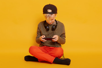 Close up portrait of little boy sitting on floor in studio with crossed legs isolated over yellow wall, watching video online on smartphone or playing game. Childhood and technology concept.