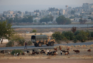 A Turkish military truck drives on the Turkish-Syrian border, with the Syrian town of Kobani in the background, in Suruc