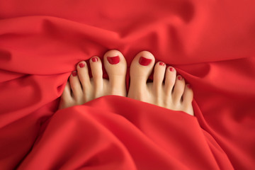 female fingers with red pedicure from under the red covers Close-up of covered female feet with red pedicure