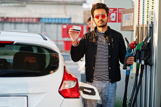 South asian man or indian male refueling his white car on gas station and hold credit card.