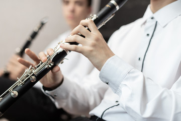 A boys with a clarinet plays music.children are engaged in music at the music school hands on a wind musical instrument close up
