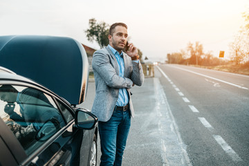 Elegant middle age business man calling towing service for help on the road. Roadside assistance concept.