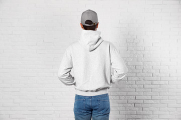 Wall Mural - Young man in sweater at brick wall. Mock up for design