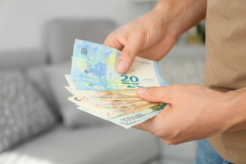 Man with Euro banknotes in room, closeup