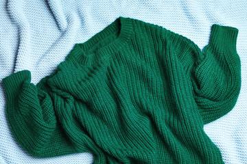 Fototapete - Warm green knitted sweater on light blue blanket, flat lay