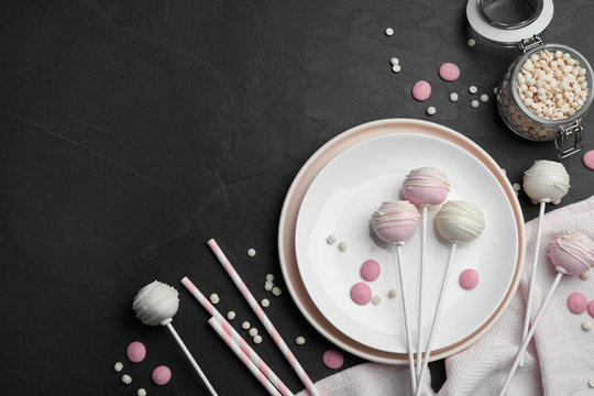 Sweet cake pops on black background, flat lay. Space for text