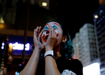 An anti-government protester with her face painted as the Joker shouts to police station during a protest on Halloween day in Hong Kong