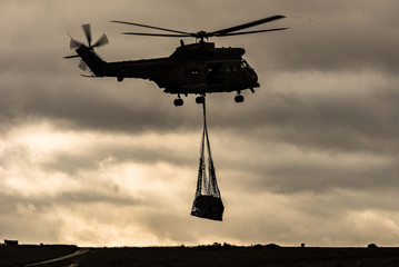 Poster Helicopter Puma military helicopter carries underslung load at dusk