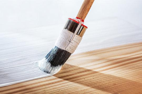 Applying white primer paint on wood