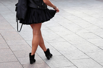 Slender girl in a short a-line skirt and black shoes. Female legs on the street background, autumn fashion, clothing and footwear