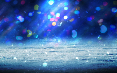 Winter abstract, blurred background with bokeh. Blurry night city lights in reflection on a snowy road. Neon light, falling snow, snowflakes.