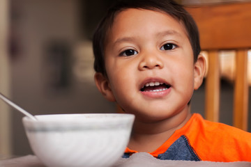 A hispanic boy at the dinner table with a bowl, spoon and ready to eat breakfast.