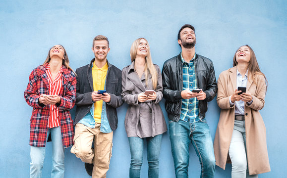 Happy friends group using smartphones against blue wall at university college break - Young people having fun with mobile smart phone - Technology addiction concept with always connected millennials