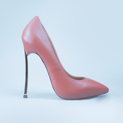 Female pink shoes on blue background