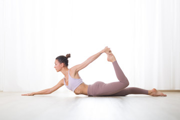 Fotomurales - Portrait of gorgeous active sporty young woman practicing yoga in studio. Beautiful girl practice Dhanurasana half bow yoga pose. Healthy active lifestyle, working out indoors in gym.
