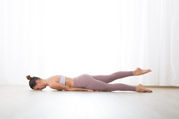 Fotomurales - Portrait of gorgeous active sporty young woman practicing yoga in studio. Beautiful girl practice Salabhasana, locust yoga pose. Healthy active lifestyle, working out indoors in gym.