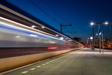 Train passing the platform on a train station in the evening. Groningen, Holland.