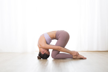 Fotomurales - Portrait of gorgeous active sporty young woman practicing yoga in studio. Beautiful girl practice Sasangasana, rabbit yoga pose. Healthy active lifestyle, working out indoors in gym.