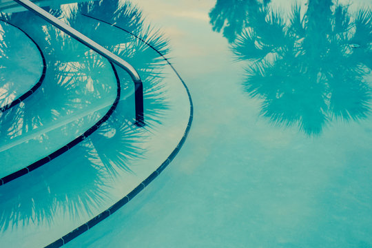 Abstract teal background with palm trees reflected into a Hollywood glamour style swimming pool.