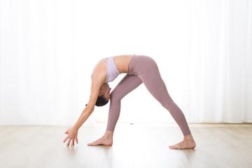 Fotomurales - Portrait of gorgeous active sporty young woman practicing yoga in studio. Beautiful girl practice Dandayamana Bibhaktapada Jauushirasana, standing separate leg head to knee pose.
