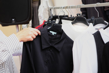 A woman chooses clothes in a store. A variety of women's clothing on hangers. Photo without a face. Hands only
