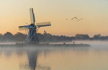 Nature awakens at a traditional Dutch windmill during a foggy sunrise. De Helper, Groningen. Fototapete