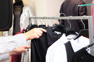A woman chooses clothes in a store. A variety of women's clothing on hangers. Photo without a face.