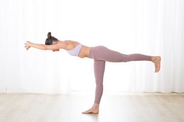 Fotomurales - Portrait of gorgeous active sporty young woman practicing yoga in studio. Beautiful girl practice Tuladandasana, balancing stick yoga pose. Healthy active lifestyle, working out indoors in gym.