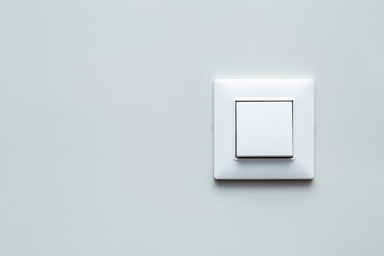 a light switch, a plastic mechanical button of white color installed on a light wall with copy space for text.