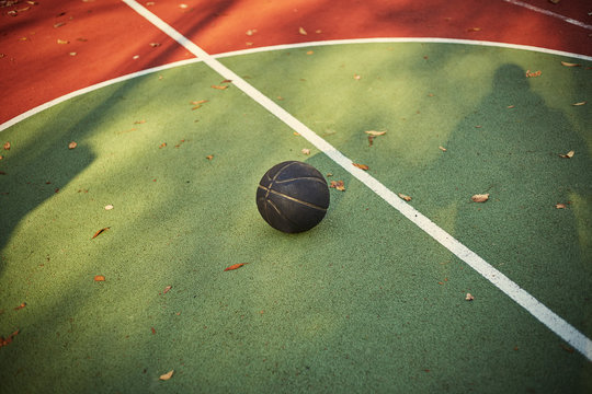 Red and green street basketball court with black ball.