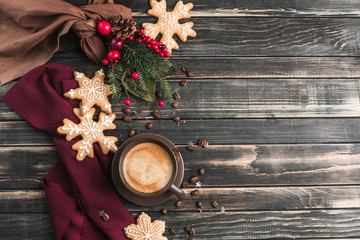 A Cup of coffee with foam on a dark wooden background with gingerbread in the form of snowflakes. New year and Christmas mood.