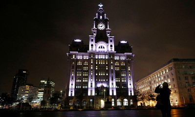An woman takes photographs of the 'Flight' installation on the front of the Royal Liver Buildings which forms part of the River of Light festival in Liverpool, Britain