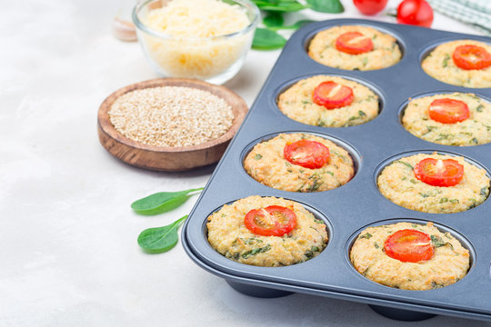 Savory muffins with quinoa, cheese and spinach topped with tomato, in muffin tin, horizontal, copy space