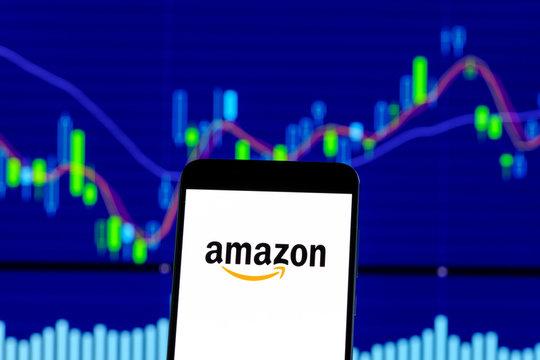 amazon logo is seen on an smartphone over stock chart