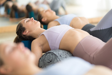 Restorative yoga with a bolster. Group of three young sporty attractive women in yoga studio, lying on bolster cushion, stretching and relaxing during restorative yoga. Healthy active lifestyle.
