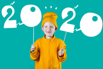 cheerful boy in a yellow hat and jacket holding the figures 2020 on bright colored background