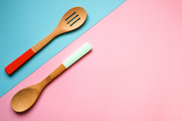 Two wooden spoons on a blue and pink background, top view, copy space
