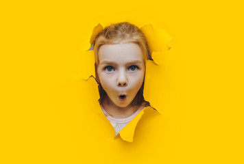 Funny red-haired child girl peeping through hole on yellow paper. The concept of surprise, fear, fright, joyful mood from what he saw. Discounts, sales, surprise. Copy space.