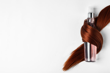 Wall Mural - Spray bottle wrapped in lock of hair on white background, top view. Natural cosmetic products