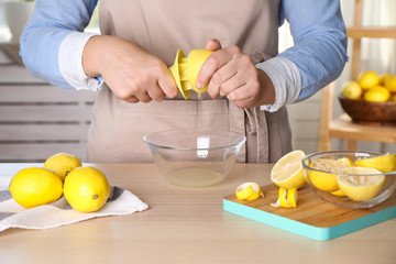Woman squeezing lemon juice with reamer at wooden table, closeup