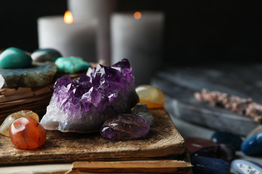 Many different gemstones and blurred candles on background