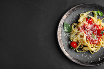 Tasty pasta on black table, top view. Space for text