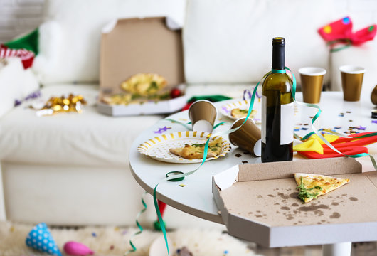 Messy table with bottle of wine and pizza indoors, space for text. Chaos after party
