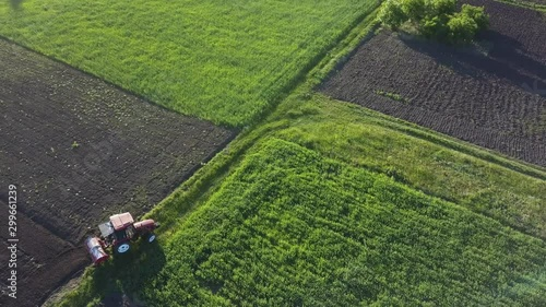 Wall mural Rural fields with crops and tractor on a sunny day. 4K video, 240fps, 2160p.