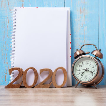 2020 Happy New Year  with blank notebook, retro alarm clock and wooden number. New Start, Resolution, Goals, Plan, Action and Mission Concept