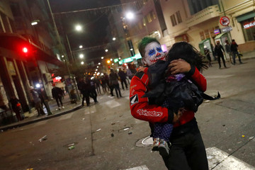 A man with make up to resemble the comic book character Joker, carries a child during a protest in La Paz